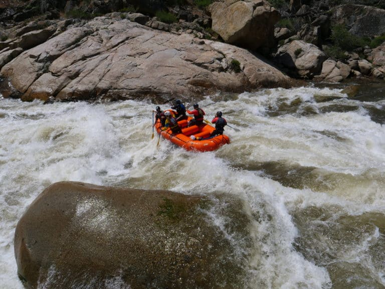 large boulders surround rafters as they navigate the river Sierra South Mountain Sports Kern River California
